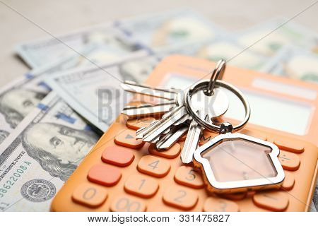Keys With House Trinket And Calculator On Money, Closeup Real Estate Agent Service