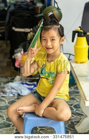 Da Nang, Vietnam - March 10, 2019: Young Girl Wearing Yellow T-shirt And Sitting On Blue Stool Flash