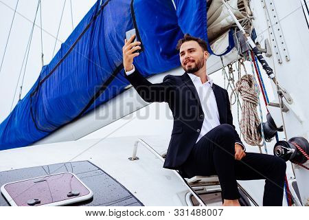 Young Handsome Businessmen Sitting On Luxury Yacht And Taking Selfies On Mobile Phone