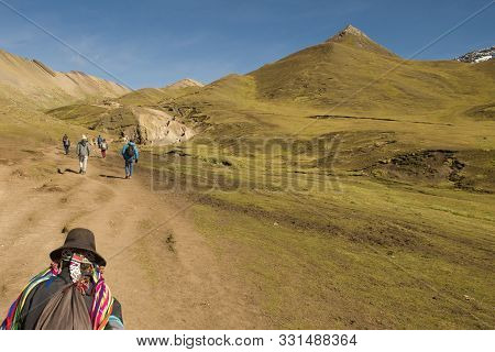 Cusipata, Peru - June 08, 2017: Peruvian Andean Man And Tourists Walking Up The Hill In The Way To V