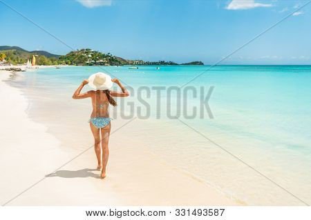 Beach travel vacation woman walking on luxury Caribbean cruise destination Antigua island in bikini wearing beach hat, carefree on holidays on Jolly Beach. Girl on travel vacation holidays swim model.