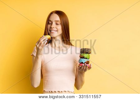Hungry Happy Caucasian Young Woman Holding Sweet Glazed Doughnuts, Eating Delicious Dessert, Having