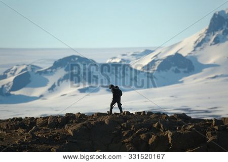 Walking on cliffs in Icelandic Highlands, snowy mountains in the background, hooded man photographer carriing a camera