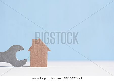 Cardboard Cutout House And Wrench On Blue Background With Copy Space. Concept Of Repair, Redevelopme