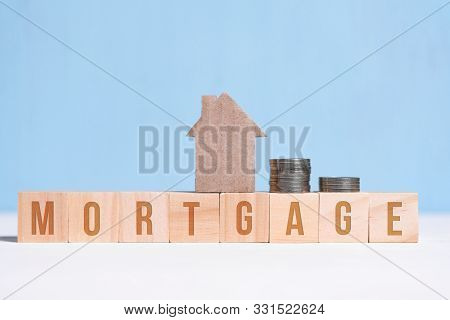 Cardboard Cutout House And Coins On Cubes With Inscription Mortgage On Blue Background. Concept Of H
