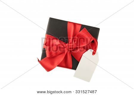 Black Gift Box With Red Satin Ribbon And Tag Isolated On White Background. Black Friday