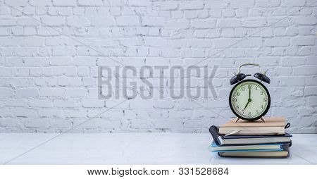 Classic Clock On Book Stack With White Brick Wall Texture Background, View From Front Table.