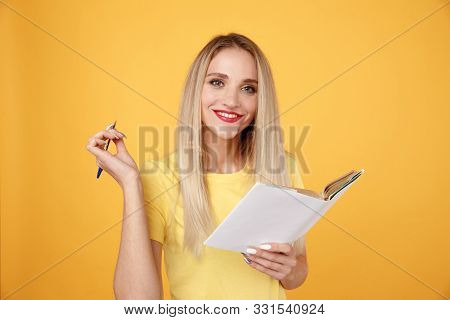 Blond Woman Making A Note By Pen In Her Diary Isolated In The Yellow Studio.