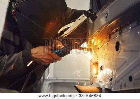 Worker Repairing Car Body With Carbon Dioxide Welding. Weld Of Auto.