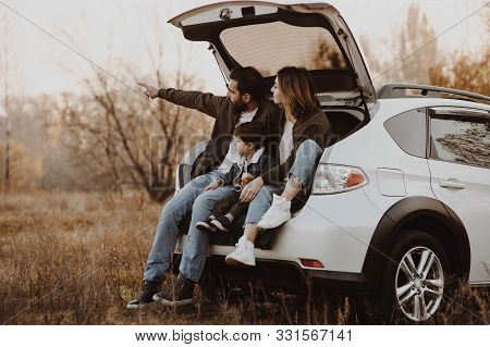 Happy Family Sitting At Open Trunk Of Hatchback Car And Pointing Finger Outdoors. Road Trip Concept.