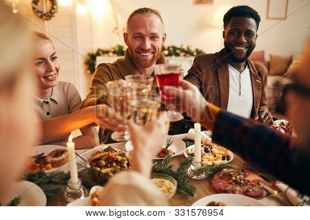 Multi-ethnic Group Of Cheerful Adult People Clinking Champagne Glasses While Enjoying Christmas Dinn