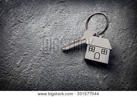 House key on a house shaped keychain on stone concept for real estate, moving home or renting property