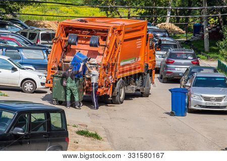 Tula, Russia - July 27, 2019: Two Workers Loading Trash Into A Garbage Truck In Parking