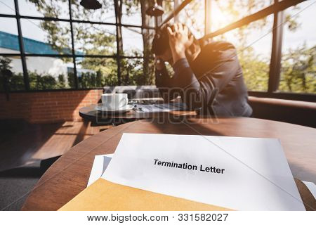 Stressed Businessman Feeling Down After Received Termination Of Employment Form In Paper Brown Envel