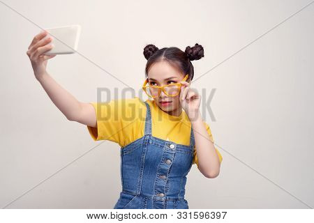 Young Pretty Asian Girl Who Wearing A Jeans Dungaree And Yellow Glasses, Taking Selfie, Smiling