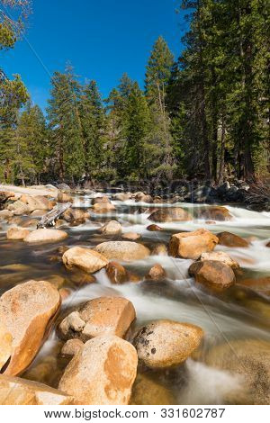 Wild Merced river with many boulders in Yosemite National Park. Long exposure. California, USA