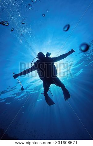 Scuba Diver In The Blue Water Descending In To The Depth