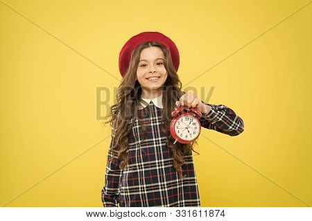 Putting Her Alarm Clock On. Happy Little Girl Holding Alarm Clock On Yellow Background. Small Child