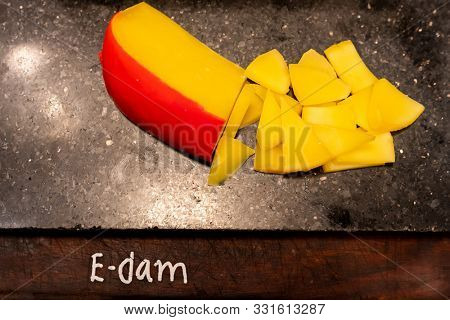 edam cheese on black stone plate in buffet line