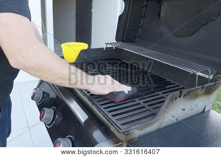The Male Hand Cleans The Black Grill With A Soft Brush. Grill For Frying Meat. Cleaning The Outdoor