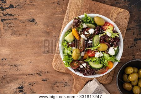 Fresh Healthy Salad On Wooden Table. Top View With Copy Space.