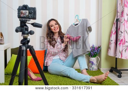 Girl Matching Clothes And Shoes. Fashion Blogger Holds T-shirt And Shoes And Filming It For Her Vide