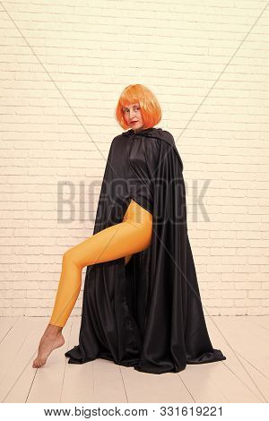 Fashion Is Her Life. Fashion Model Wearing Orange Wig Hair And Black Robe On White Brickwall. Sexy G