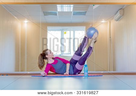 Beautiful Young Woman Doing Pilates Workout With Small Blue Fitness Ball. Healthy Lifestyle Concept.