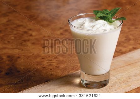 Kefir In A Glass Goblet With A Mint Branch On A Wooden Board On A Brown Background