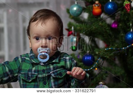 A Little Boy In A Green Shirt With A Pacifier Stands At The Holiday Tree.