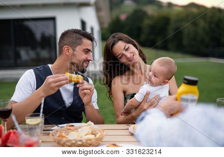 Young Couple With Baby Sitting At Table Outdoors On Family Garden Barbecue.