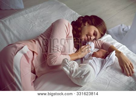 Mom With A Small Newborn Daughter Lying On The Bed