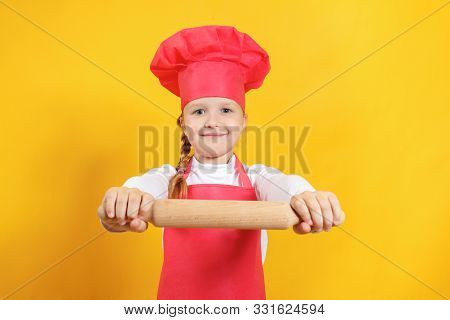 Beautiful Little Girl Chef On A Yellow Background. The Child Holds In His Hands A Wooden Rolling Pin