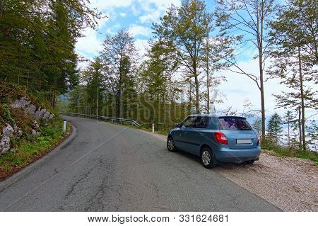 A Narrow Asphalt Mountain Road In Slovenia. Beautiful Landscape View Of Ancient Forest And Mountain