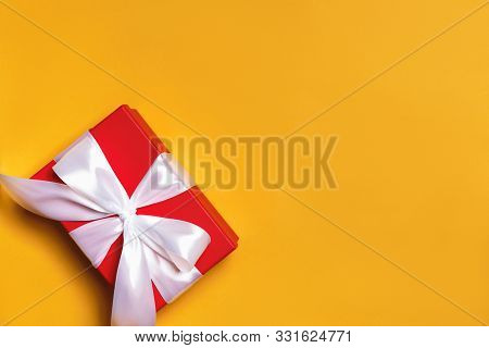 Close Up Of A Red Box With A Gift And A White Ribbon On A Yellow Background.