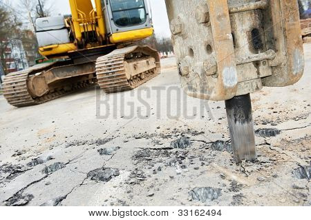 Excavator breaking street asphalt with hydrohammer drill at repairing roadwork
