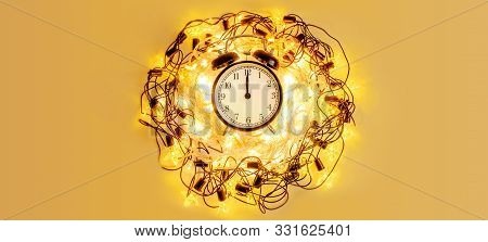 New Year Alarm Clock Surrounded With Festive Star Garland On Yellow Background.