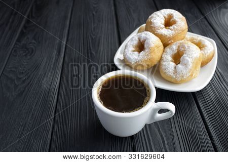Black Coffee In The White Cup And Homemade Donut With Powdered Sugar On The Black Wooden Background.