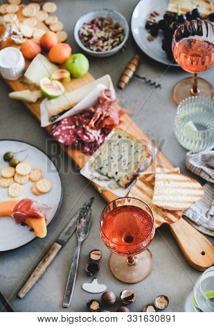 Mid-summer Picnic With Rose Wine, Cheese, Charcuterie, Appetizers And Fruits