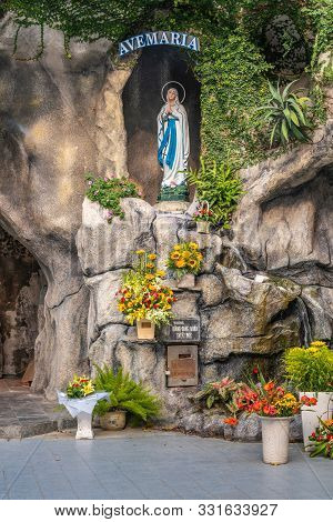 Da Nang, Vietnam - March 10, 2019: Closeup Of Holy Virgin Mary In Grotto Outside Cathedral. Gray Sto