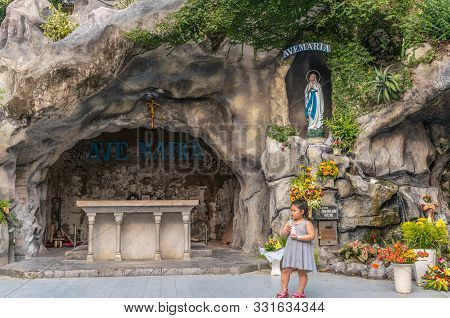 Da Nang, Vietnam - March 10, 2019: Little Girl In Front Of Virgin Mary Grotto Outside Cathedral. Sta