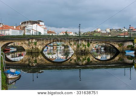 Bridge In A Estuary With Boats On Its Sides And Reflects