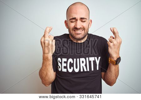 Young safeguard man wearing security uniform over isolated background gesturing finger crossed smiling with hope and eyes closed. Luck and superstitious concept.