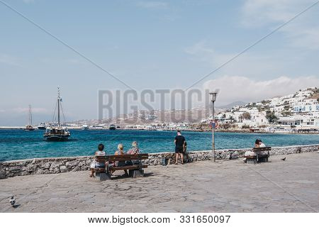 Mykonos Town, Greece - September 23, 2019: People Relaxing On A Bench By The Water On A Sunny Day In