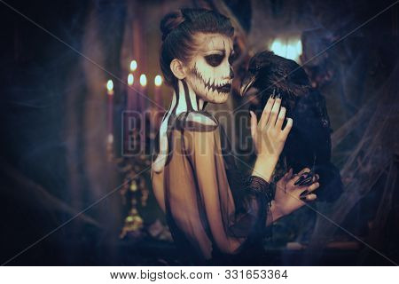 Beautiful elegant lady with skull pumpkin makeup stands with black raven in the old castle decorations. Vintage style. Halloween. Day of The Dead.