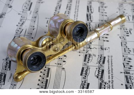 Vintage mother of pearl opera glasses made by Iris Paris on an operatic score poster