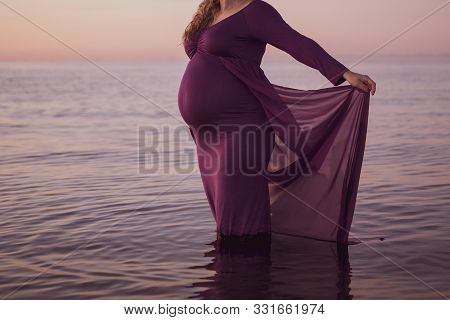 Portrait Of Beautiful Pregnant Woman In A Purple Dress Touching Her Stomach, Standing Outside In The
