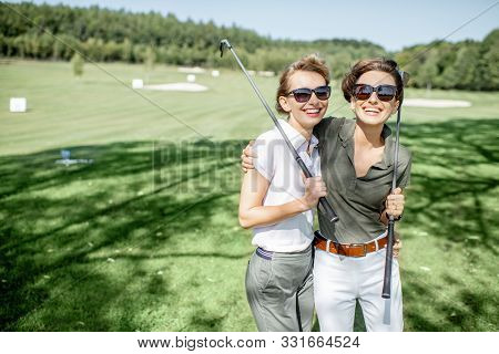 Portrait Of A Two Female Best Friends Standing With Golf Equipment On A Playing Course, Talking And