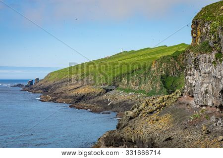View On The Mykines Island With Moody Clouds Covering The Top Of The Mountains And Sheep Grazing On