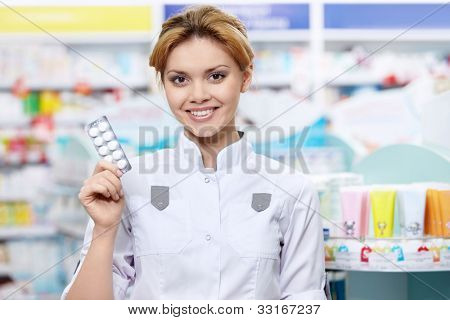The pharmacist at the pharmacy with tablets